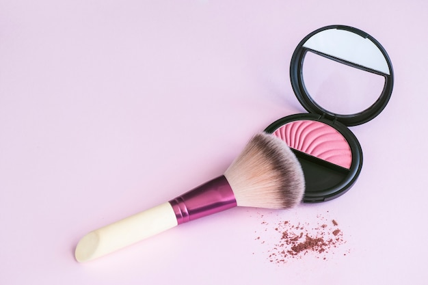 Make-upborstel die op een roze rouge op roze achtergrond leunen Premium Foto