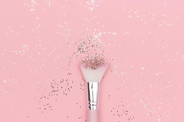 Make-upborstel en glanzende sparkles op pastelroze. feestelijk magisch make-upconcept. Premium Foto