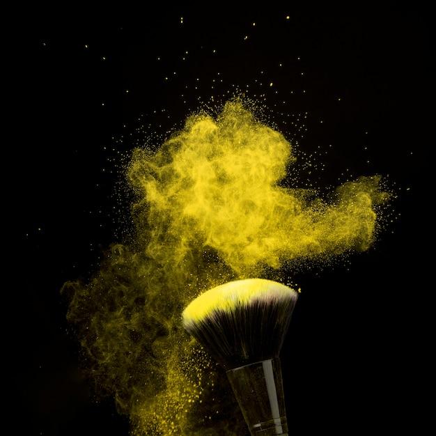 Make-upborstel in geel poederstof op donkere achtergrond Gratis Foto