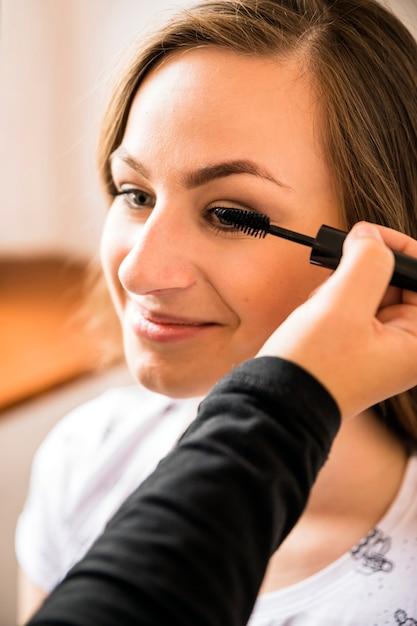 Make-upkunstenaar die mascara op het gezicht van de gelukkige vrouw toepassen Gratis Foto