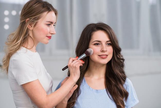 Make-upkunstenaar die modelgezicht behandelen door poeder Gratis Foto