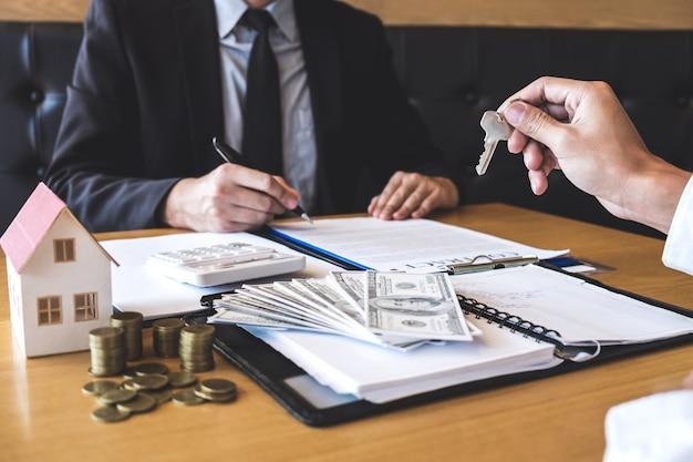 Makelaar die huissleutels aan cliënt geeft na ondertekening overeenkomst contract onroerend goed met goedgekeurd hypotheekaanvraagformulier, betreffende hypothecaire leningaanbieding en huisverzekering Premium Foto