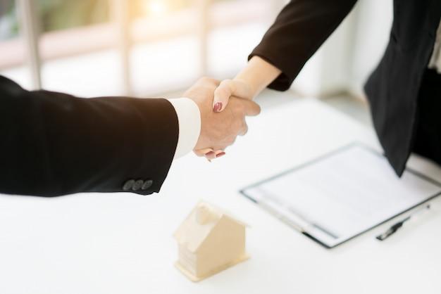 Makelaar in onroerend goed en klant handen schudden na ondertekening van een contract Premium Foto