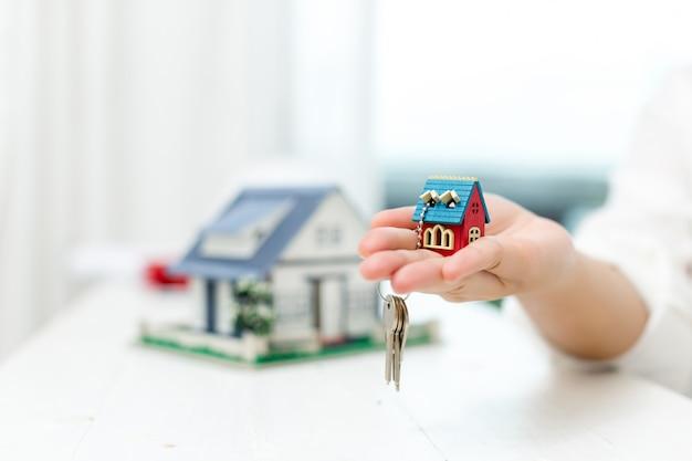 Makelaar in onroerend goed met huismodel en sleutels Gratis Foto
