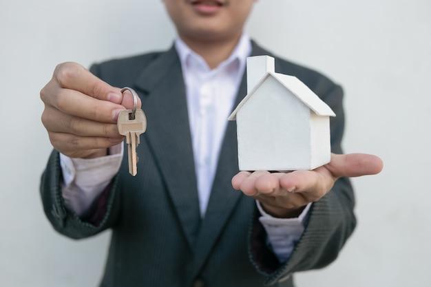 Makelaar in onroerend goed met huismodel en sleutels Premium Foto