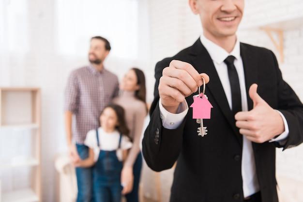 Makelaar in zwart pak heeft sleutels in de vorm van een huis. Premium Foto