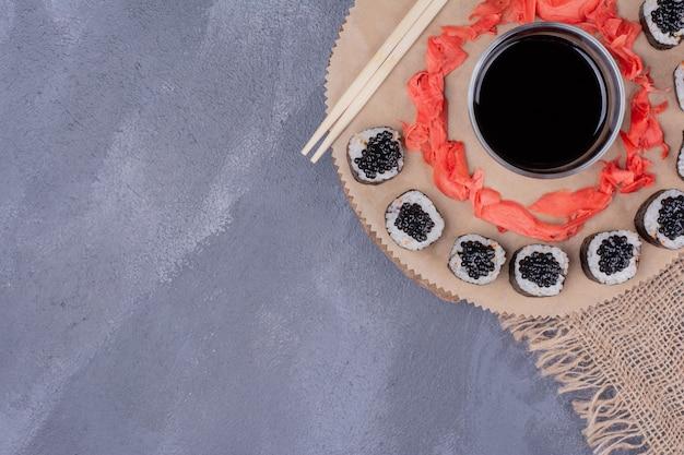 Maki sushi rolt op houten plaat met stokjes, ingelegde gember en sojasaus. Gratis Foto