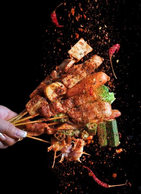 Mala gegrilde barbecue (bbq) met sichuan peper, met vallende smaakmakers mala poeder en chili, heet en pittig en heerlijk streetfood. Premium Foto