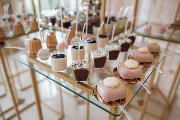 Mallen met portiedesserts en koekjeskoekjes bedekt met roze room staan op de reep Gratis Foto