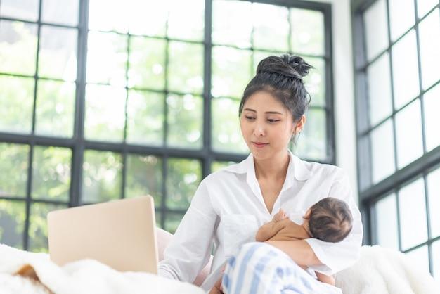 Mam is het opvoeden van een baby tijdens het werken thuis. Premium Foto