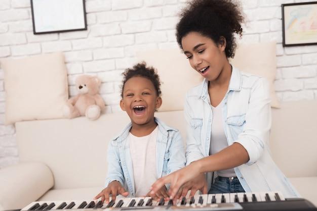 Mam leert een klein meisje om piano te spelen. Premium Foto