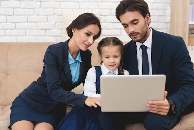 Mama en papa met dochter ingeschakeld kijken naar de laptop. Premium Foto