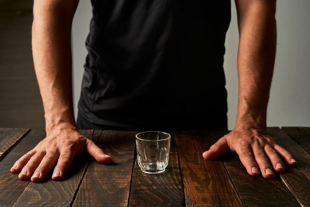 Man aan een bar met een borrelglas. concept van alcoholisme en verslaving. Premium Foto