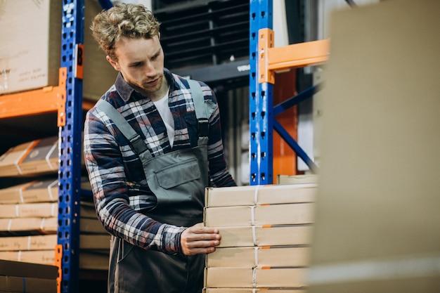 Man aan het werk in een carboard fabriek Gratis Foto