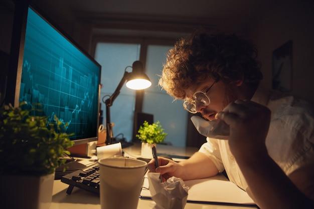 Man aan het werk in kantoor alleen tijdens coronavirus of covid-19 quarantaine, tot laat in de nacht Gratis Foto