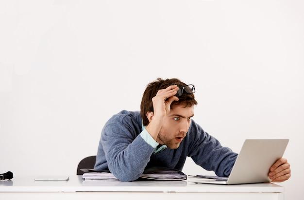 Man aan het werk in kantoor, startbril en staren verward met ongeloof laptopscherm, schokkend nieuws lezen, nieuwsgierig rapport ontvangen Gratis Foto