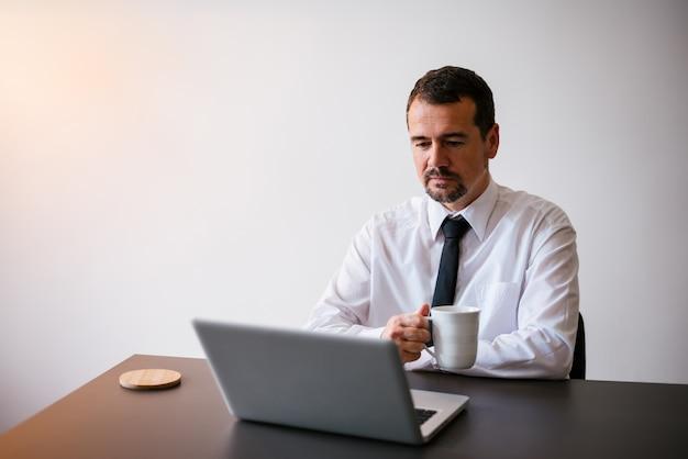 Man aan het werk met laptop thuis, met een kopje warme thee of koffie. Premium Foto