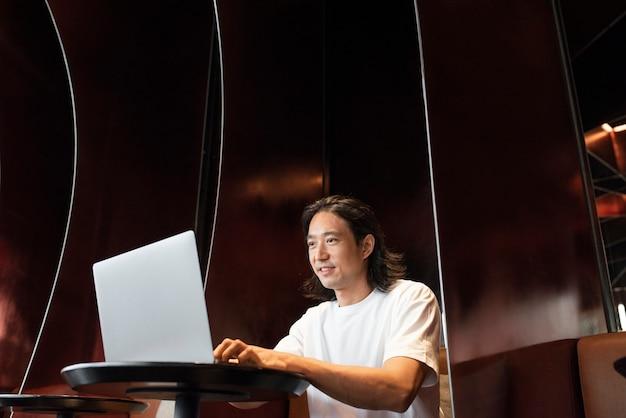 Man aan het werk op een laptop op een moderne co-working-ruimte Gratis Foto