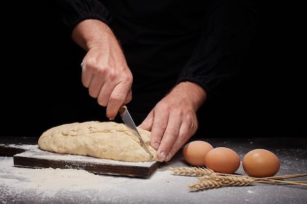 Man baker en zijn handen over het brood van volkoren meel Premium Foto