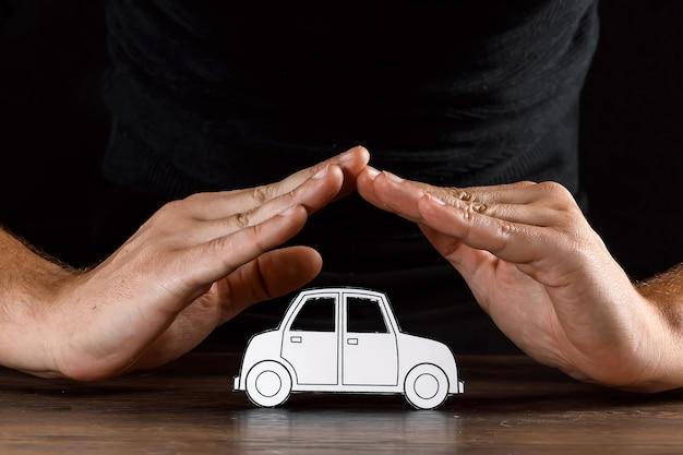 Man bedekt een papieren auto met zijn handen Premium Foto