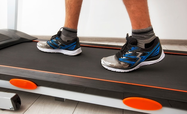 Man benen in sneakers op loopband Premium Foto