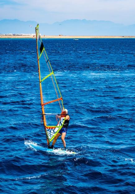 Man besteden vrije tijd met extreme windsurfen sport in blauwe zee met zandstrand op achtergrond Premium Foto