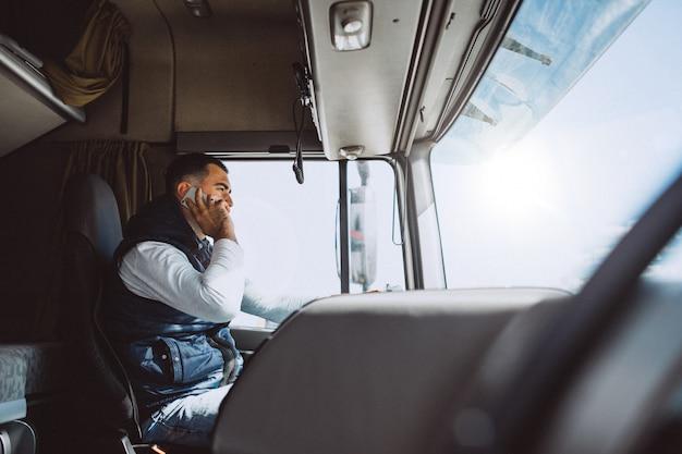 Man bestuurder van de vrachtwagen in een logistiek bedrijf Gratis Foto
