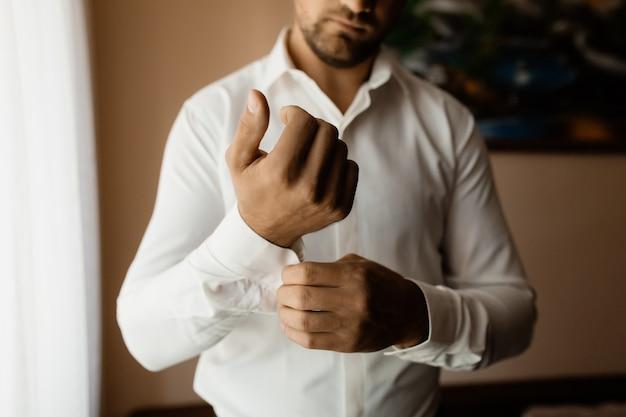 Man bevestigt een knop op zijn mouw Gratis Foto