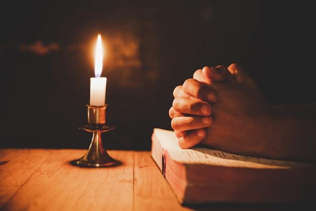 Man bidden op de bijbel in het licht kaarsen selectieve aandacht Gratis Foto