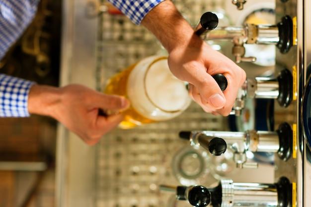 Man bier puttend uit kraan Premium Foto