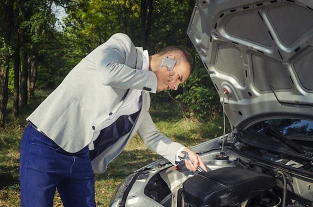 Man bij de open motorkap die een telefoongesprek voert en probeert het voertuig te repareren Gratis Foto