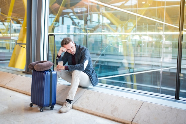 Man boos, verdrietig en boos op de luchthaven zijn vlucht is vertraagd Premium Foto