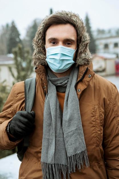 Man buiten in de winter medische masker dragen Gratis Foto
