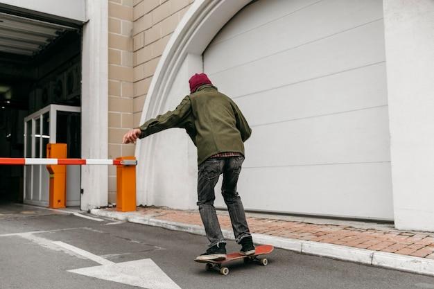 Man buiten met skateboard in de stad Gratis Foto