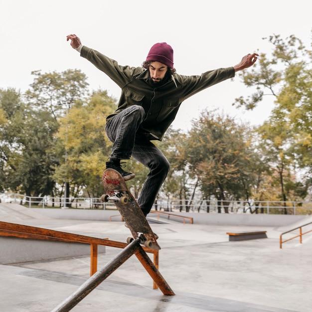 Man buiten met skateboard in het park Premium Foto