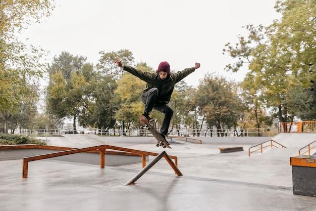 Man buiten met skateboard in het park Gratis Foto