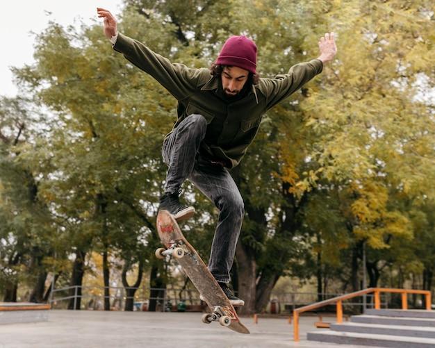 Man buiten met skateboard Gratis Foto