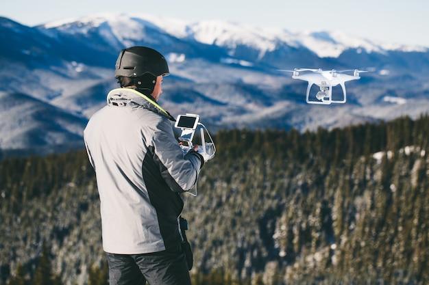 Man buitenshuis met afstandsbediening vliegt een drone in de bergen Premium Foto