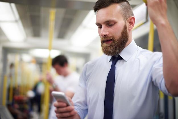 Man controleert nieuws in de mobiele telefoon in de metro Gratis Foto