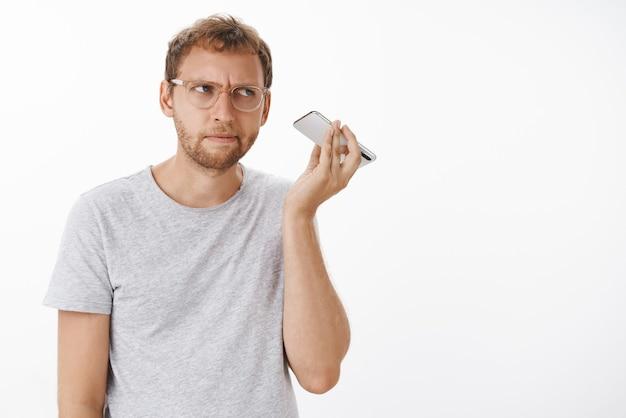 Man die audiobericht luistert, kan niet begrijpen welk vreemd geluid er uit de dynamiek komt, terwijl hij de smartphone bij het oor houdt en opzij staart met een intense gefocuste uitdrukking die zich op het geluid concentreert Gratis Foto