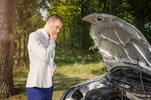 Man die bij de open motorkap staat en probeert het voertuig te repareren Gratis Foto