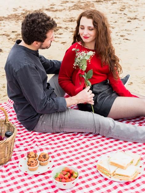 Man die bloemen geeft aan de vrouw op geruite dekbed Gratis Foto