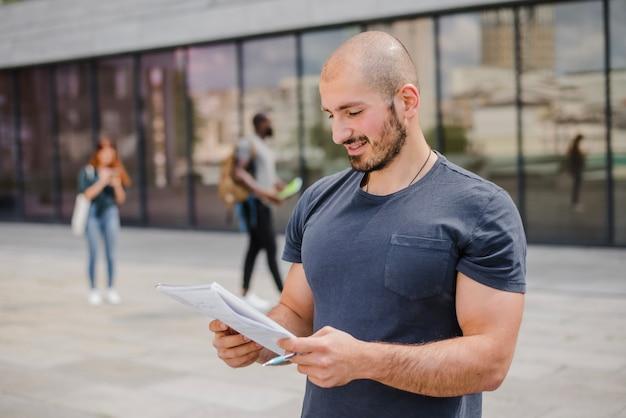 Man die buiten de notitieblok en pen bevindt Gratis Foto