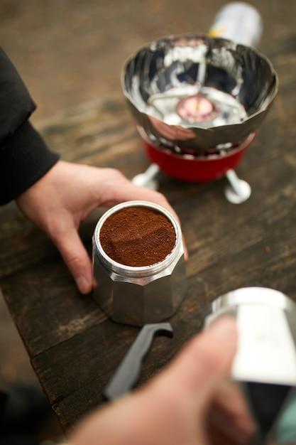 Man die camping koffie buiten maakt met metalen geiser koffiezetapparaat op een gasbrander, stap voor stap. Premium Foto