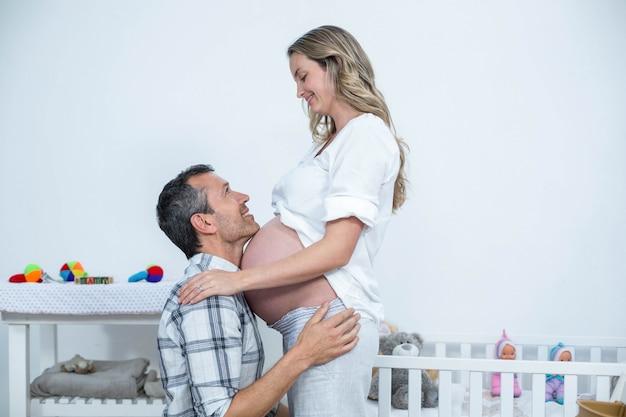 Man die de buik van zwangere vrouw thuis aanraken Premium Foto