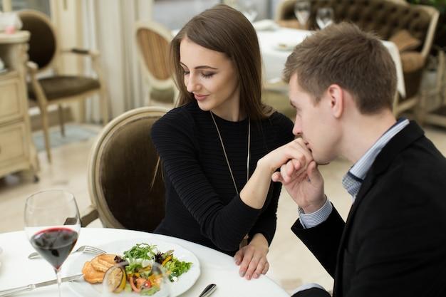 Man die de hand van een vrouw kust bij een romantisch diner terwijl ze hem met een bewonderende uitdrukking en een mooie glimlach bekijkt Premium Foto