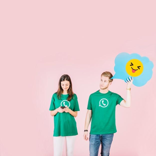 Man die emoticon met uitgestoken tong naast vrouw met behulp van mobiele telefoon Gratis Foto