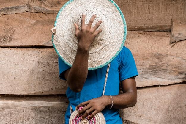 Man die gezicht bedekt met hoed Gratis Foto