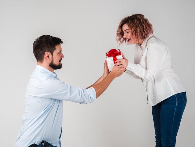 Man die gift geeft aan vrouw voor valentijnskaarten Gratis Foto