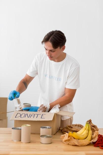 Man die goodies in donatieboxen plaatst Gratis Foto